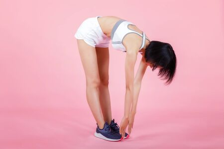 Side view of beautiful young woman in sportswear doing stretching her hamstrings isolated on pink background.
