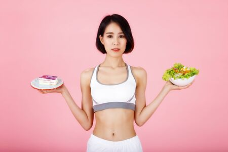 Young woman choosing between piece of cake and healthy salad isolated on pink background. Healthy eating, diet, nutrition, weight loss concept. Reklamní fotografie