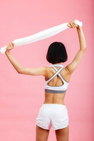Young asian woman with towel and headphone on neck isolated on pink background. Healthy lifestyle concept. Фото со стока