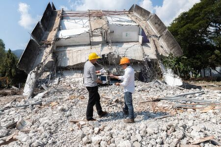 Demolition control supervisor and contractor discussing on demolish building. Фото со стока