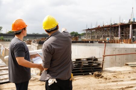Team of construction workers discussing project details with blueprint in construction site.