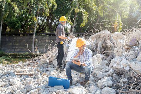 Demolition control supervisor and contractor working on demolish building. Фото со стока