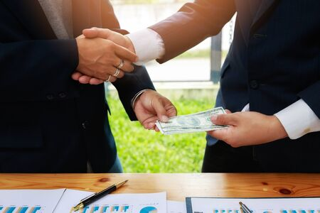 Businessman handshake and dollar banknotes in hands. Dishonest cheating in business illegal money,Bribery and corruption concept. Bank customers come to negotiate a loan to invest.