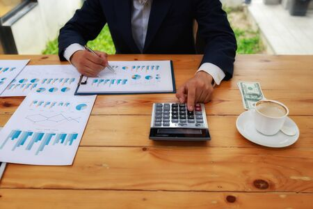 Businessmans hands using calculator and Financial data analyzing on wooden desk at the office