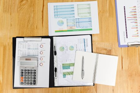 Top view of business charts or graphs, calculator notebook and pen on desk.