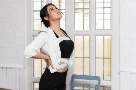 Office syndrome concept. Businesswoman twisting the body to relieve fatigue, suffering from pain after sedentary working in incorrect posture.