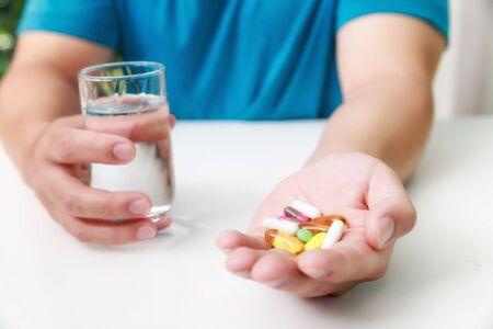 Zamknij się kolorowe pigułki, leki kapsułki i szklankę wody w rękach mężczyzny. Koncepcja opieki medycznej i zdrowia lub choroby. Zdjęcie Seryjne