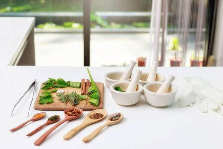 Herbal medicine preparation with fresh herbs and dried flowers, aromatherapy essential oil and mortar with pestle used in natural alternative remedies on white table. 스톡 콘텐츠