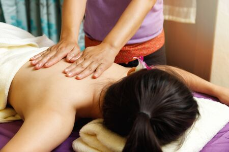 Asian woman enjoying back massage in massage salon. Beauty treatment concept. Stock Photo