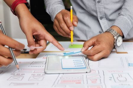 UX or UI designers designing on their smartphone application layout prototype project.