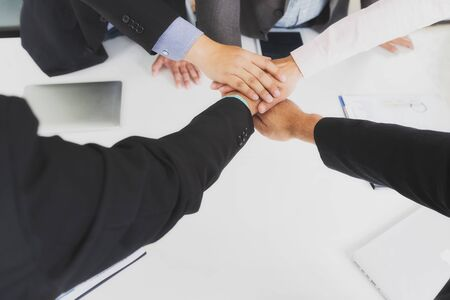 Concept of teamwork: Close-Up of hands business team showing unity with putting their hands together.