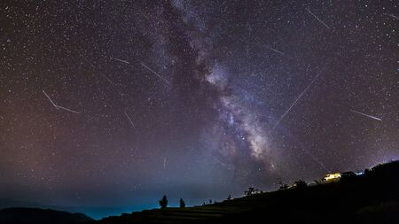 Long time exposure night landscape with the milky way during meteor shower over a mountain with hut.