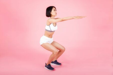 Side view of young woman in sportswear doing squat isolated on pink background. Healthy lifestyle concept.