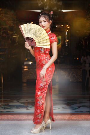 Chinese woman in a red cheongsam dress holding fan at shrine. Concept to celebrate Chinese New Year.