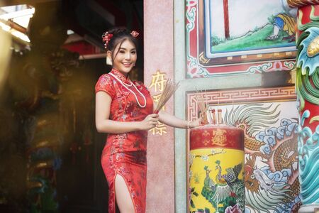 Concept to celebrate Chinese New Year, Vegetarian Festival : Chinese woman in a red cheongsam dress holding incense pay homage to Chinese god at shrine. Stok Fotoğraf
