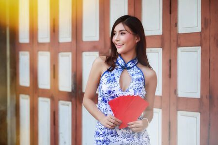 Chinese woman in cheongsam (qipao) dress holding red envelopes (hong bao). Concept to celebrate Chinese New Year. Stok Fotoğraf
