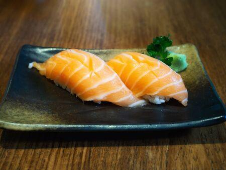 Salmon sushi set in black ceramic disk. Japanese cuisine. Foto de archivo