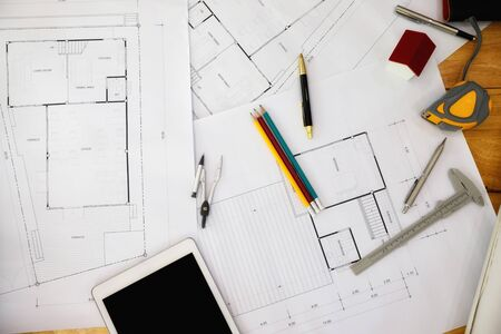 Construction blueprints with tools and tablet, top view. Tablet with architectural blueprints and measuring tools on wooden table.