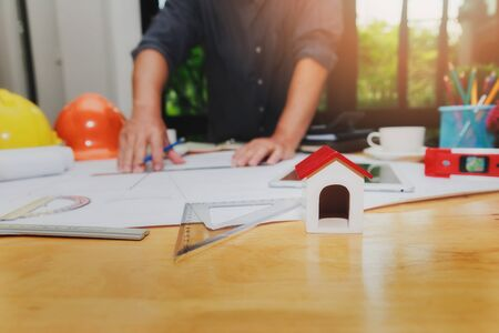 Close up of a house model on the desk with architect working with blueprint construction project in home office.