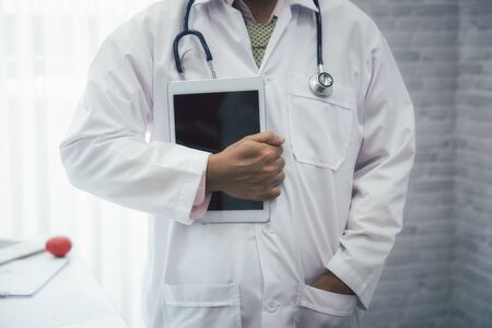 Doctor standing with stethoscope and holding tablet computer. Technology and medical concept.