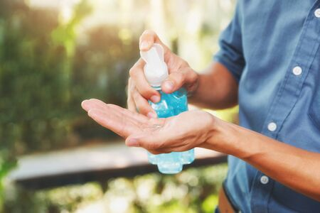 A man using alcohol based hand sanitizer for cleaning hands before working. Anti bacteria and protect from Coronavirus Disease 2019 (COVID-19) virus outbreaks.