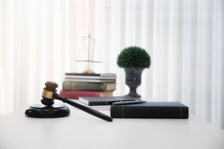 Wooden gavel and books on table in lawyer's office.