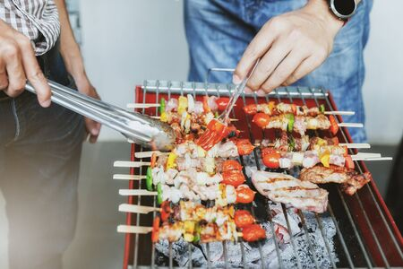 Men grilling pork and barbecue in dinner party. Food, people and family time concept. Standard-Bild