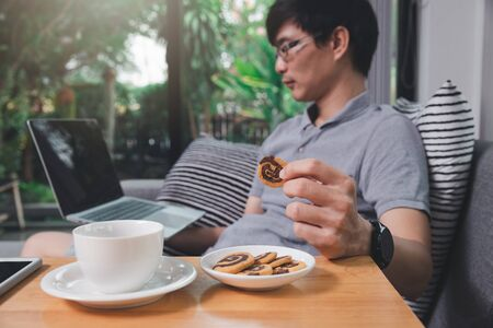 A man in casual wear picks up cookies while he is working at home office.