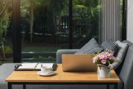 Work desk with a laptop and a notebook for working from home. Due to the spread of covid-19 worldwide, there are policies or resolutions to work at home to prevent, avoid being too close to people.