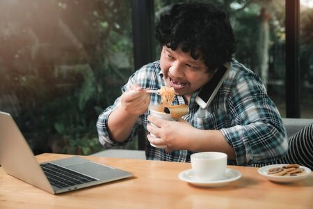 A man who works from home is busy talking on the phone with colleagues about work and eating instant noodles. While his eyes stared at the work content on the laptop as well.