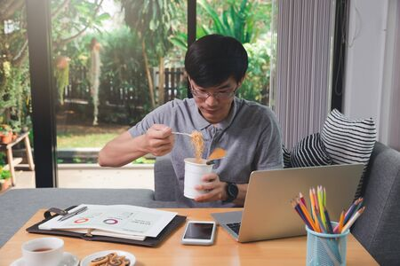 Asian man eating instant noodles while working on laptop at his home office.