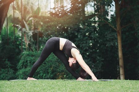 Asian woman practicing yoga in Intense Side Stretch Pose on the mat in outdoor park.
