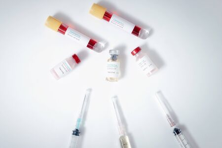 Top view of vaccine, blood samples in tubes and syringes on work table in a medical examination lab.