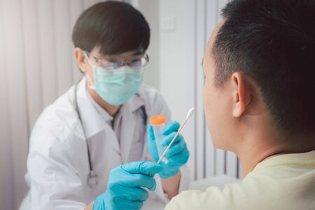 Doctor or medical staff is collecting secretions from patient for examination in the lab. Pandemic Coronavirus, COVID-19.