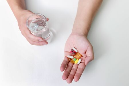 Top view of Colorful pills, capsule medicines and glass of water in man's hands. Treating COVID-19 at home on the doctor's recommendations.