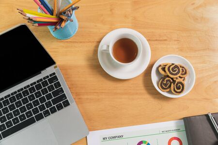 Top view of tea, cookies, Laptop with blank screen and pencils on desk in home office.