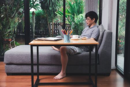 A man in casual wear uusing laptop while he is working at home office.