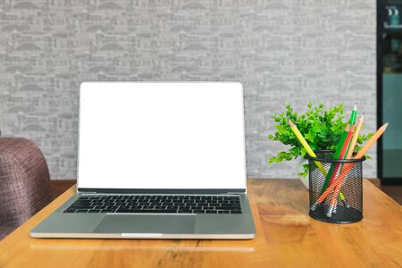 Laptop with blank screen, pencils, vase on table in home office. Workspace with laptop and office supplies.