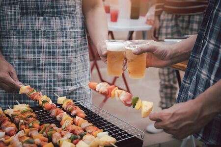 Young men cheers for a drink at a BBQ party between friends. Food, drink, people and family time concept.