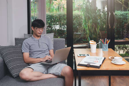 A man in casual wear using laptop while he is remotely working at home office.