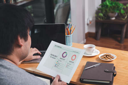 Young asian man holding document and working on laptop while sitting near window in home office.