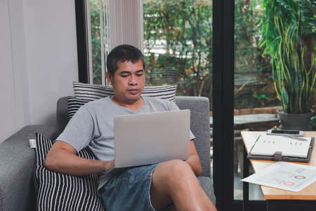 A man in casual wear using laptop while he is working at home office.