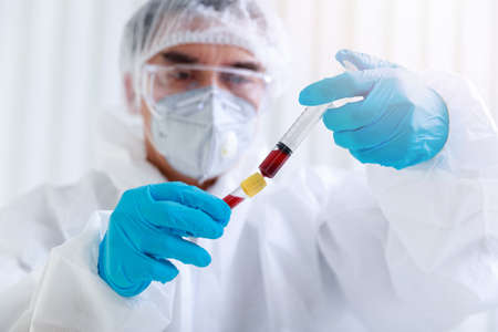 Researcher or scientists loads blood samples into test tube in laboratory. Researchers are inventing vaccines to treat COVID-19 virus.