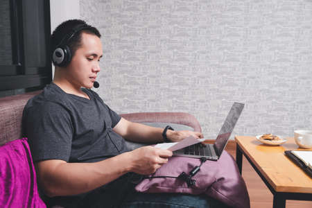 Businessman meeting online via video call on laptop in home office. Man wear headphone video calling or distance education e-leaning online course.
