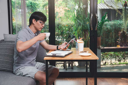 Young asian man holding a cup of coffee and using smartphone while sitting near window in home office.