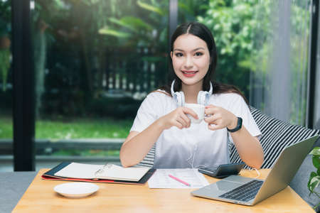 Beautiful asian woman holding cup, smiling and looking at camera in living room. Working, Learning from home concept.
