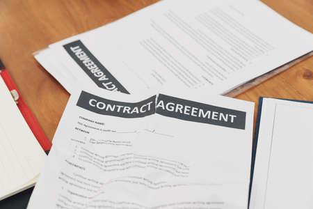 The torn contract paper placed on the table after negotiation fails. The concept of contract termination. Break the contract concept.