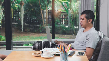 A man in casual wear using laptop while he is working at home office. Stock fotó