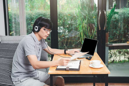 Businessman video call with clients on laptop in home office. Man wear headphone video calling or distance education e-leaning online course. Archivio Fotografico