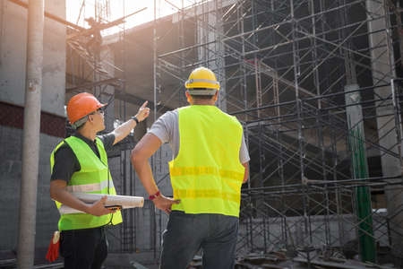 Engineer discussing with foreman about project in building construction site. Banque d'images
